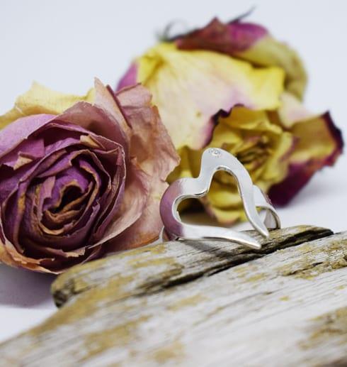 hjärtformad silverring på träbit med rosor bakom