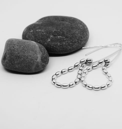droppformade silverörhängen på vit bakgrund med stenar bredvid