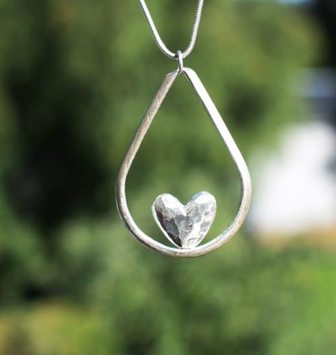 droppformat silverhalsband med hjärta i mitten hängande i luften utomhus med grön bakgrund