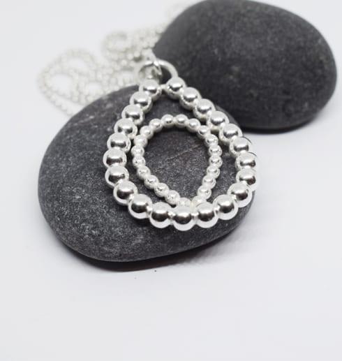 silversmycke på kultråd på grå stenar