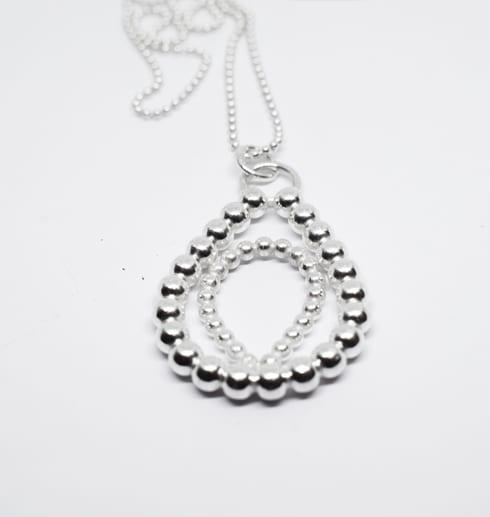 stort silversmycke i kultråd med vit bakgrund