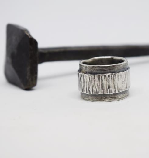 bred silverring med hamring och oxidering på vit bakgrund med järnspik