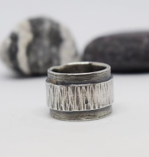 silverring med oxidering med stenar i bakgrunden