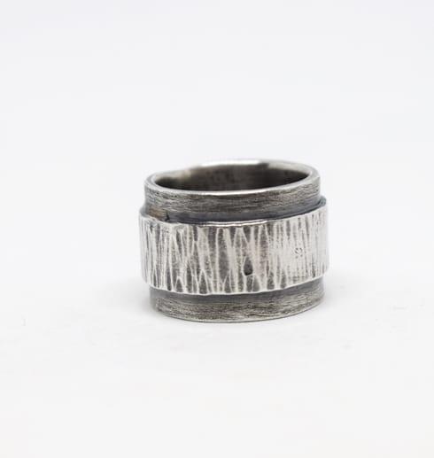 silverring med hamring och svartoxidering mot vit bakgrund