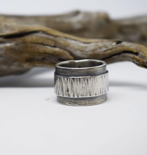 svartoxiderad bred silverring med träpinne i bakgrunden