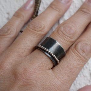 svartoxiderad stresshanteringsring på finger