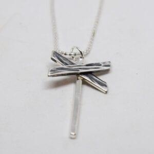 ledkryss i silver som hänger i en kedja på vit bakgrund