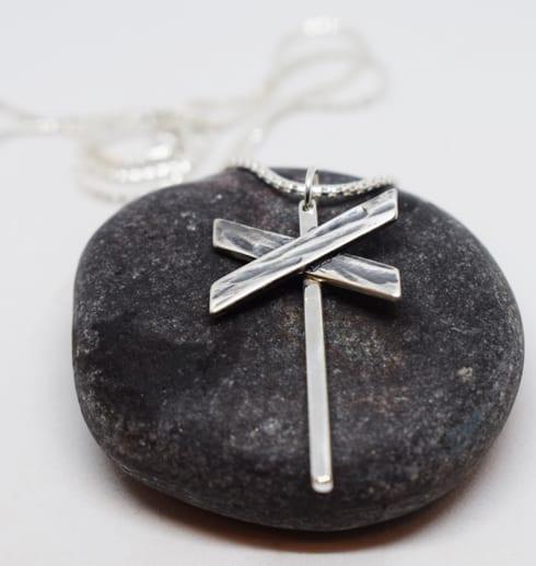 ledkryss i silver som hänger i en kedja som ligger på en mörkgrå sten