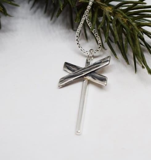 ledkryss i silver som hänger i en kedja på vit bakgrund med granris bakom