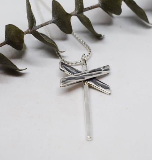 ledkryss i silver som hänger i en kedja på vit bakgrund med grön trädkvist bakom
