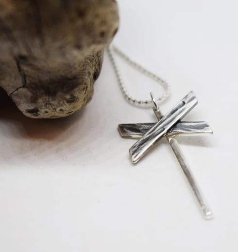 ledkryss i silver som hänger i en kedja på vit bakgrund med trädgren bredvid