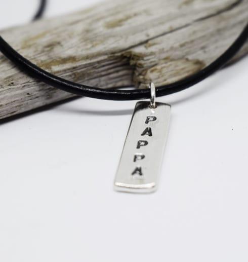 silverbricka med texten PAPPA i läderrem på vit bakgrund med träbit