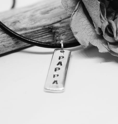 silverbricka med texten PAPPA hängande i läderrem med träbit och ros i svartvitt
