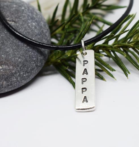 silverbricka med texten PAPPA som hänger i en läderrem med stenar och grankvist