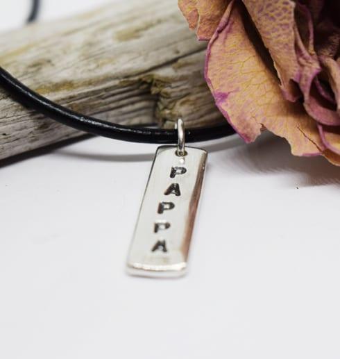 silverbricka med texten PAPPA som hänger i en läderrem med ros och träbit
