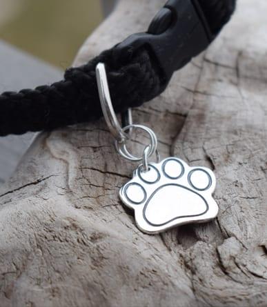 tassberlock i silver på hundhalsband liggandes på en träbit