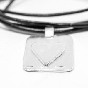 bricka med hjärta i silver i läderrem på vit bakgrund