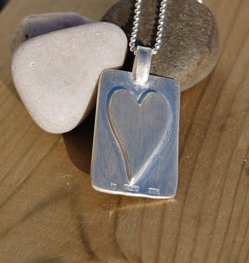 bricka med hjärta i silver på trä med stenar