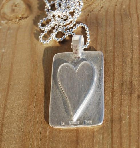 bricka i silver med hjärta på trä utomhus