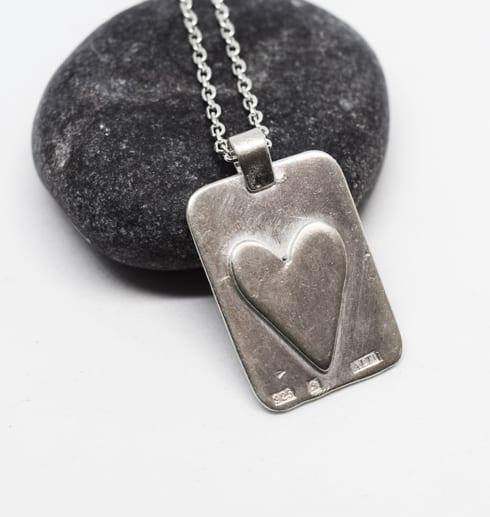 bricka med hjärta i silver på grå sten med vit bakgrund