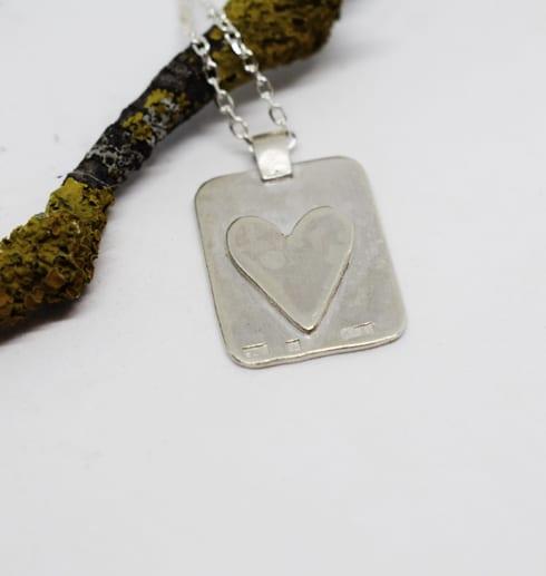 silverbricka med hjärta på vit botten med trädgren