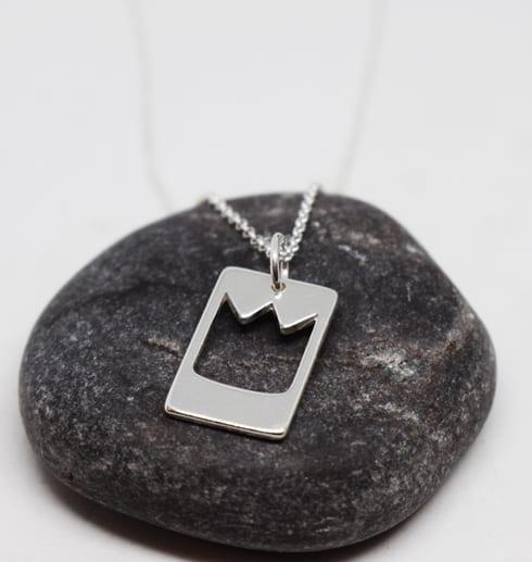 smycke med prinskrona på en grå sten