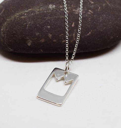 smycke med prinskrona mot vit bakgrund och en lila sten