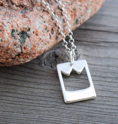 smycke med prinskrona mor trä och en röd sten utomhus