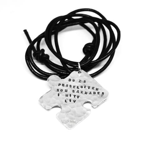 pusselbit i silver med text med vit bakgrund
