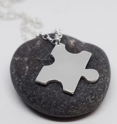 pusselbit i silver som hänger i en kedja på grå sten