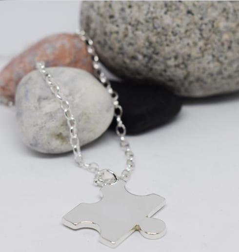 pusselbit i silver som hänger i en kedja på vit bakgrund med stenar bakom
