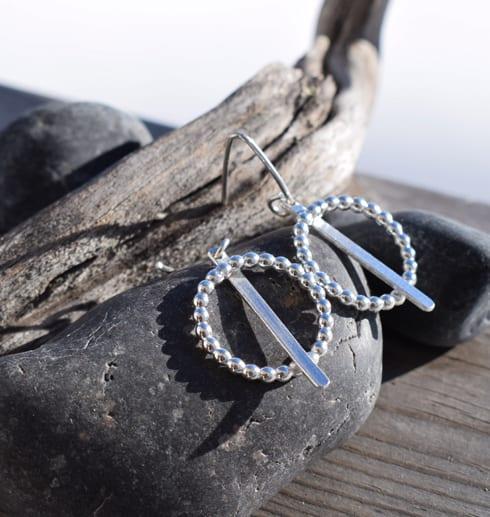 silverörhängen på sten med träbit utomhus