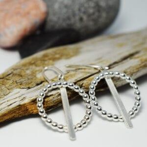 silverörhängen mot träbit och stenar bakom
