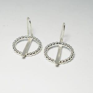 silverörhängen på vit botten