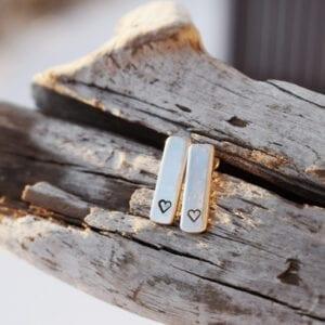 silverörhängen med hjärtan på träbit utomhus