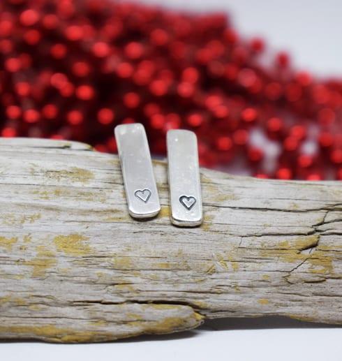 silverörhängen med hjärtan på träbit med röda kulor bakom