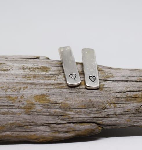 silverörhängen med stansade hjärtan på träbit