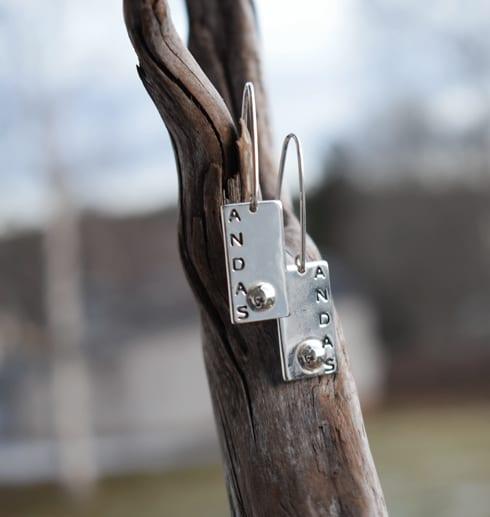 silverörhängen med texten ANDAS hängande på gren utomhus