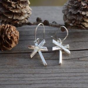 ledkryssörhängen i silver på trä med kottar bakom utomhus