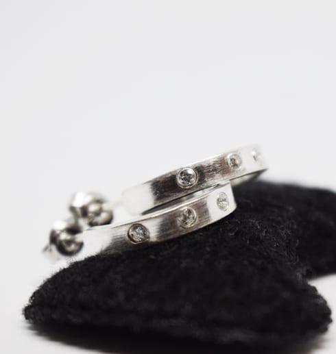 silverörhängen med stenar ppå svart sammetskudde med vit bakgrund