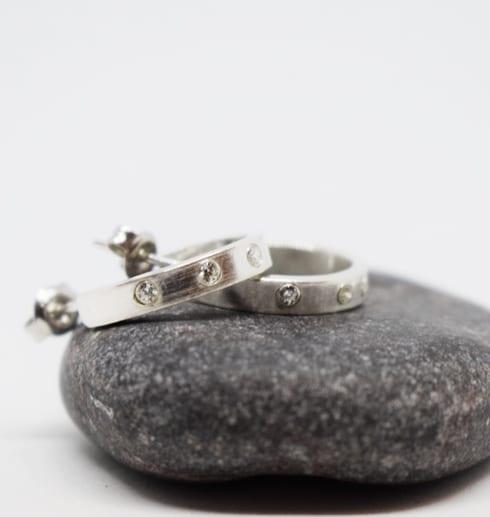 silverörhängen med stenar på en grå sten