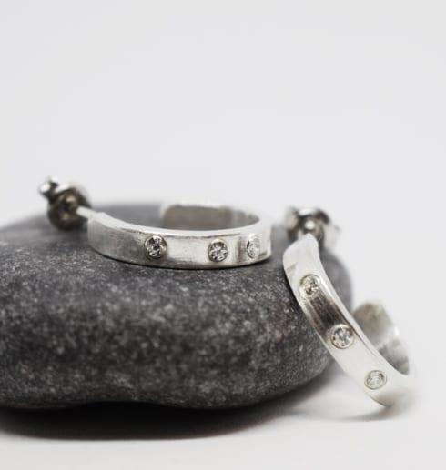 silverörhängen med stenar på grå sten med vit bakgrund