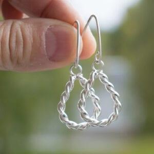 örhängen i tvinnad silvertråd utomhus som hålls med fingrar utomhus