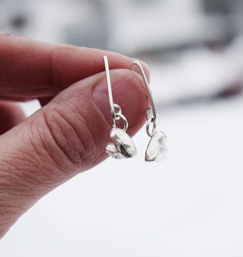 silverörhängen i form av örhängen som hålls i fingernypa
