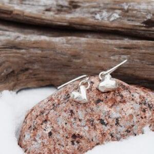 silverörhängen i form av hjärtan på röd sten med snö och trä utomhus