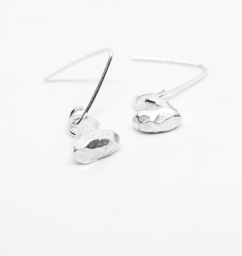 silverörhängen i form av hjärtan på vit botten