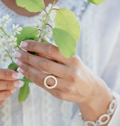 hand med gröna blad och vit blus med ring på fingret och armband runt handleden
