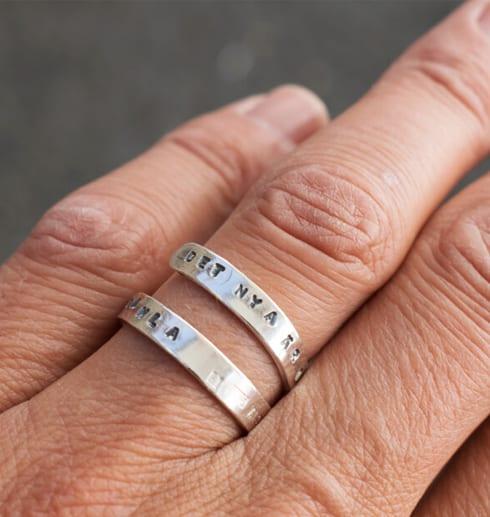 silverring med text på finger utomhus