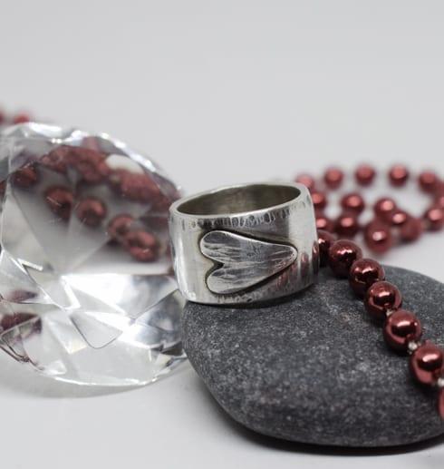 silverring med liggande hjärta på sten med diamant och röda kulor bakom