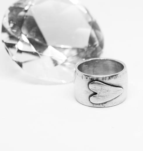 silverring med liggande hjärta på vit botten med diamant bredvid